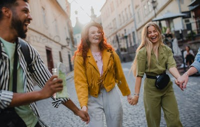 Front view of group of laughing young people outdoors on street on town trip, walking