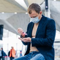 Man in medical face mask, uses disinfectant spray for hands, protects from coronavirus