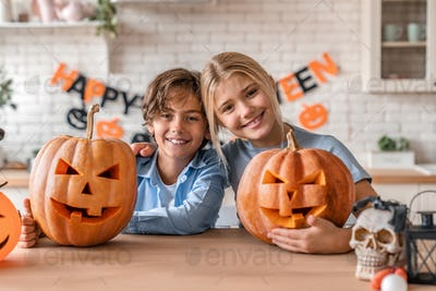 Young boy and his sister having fun with pumpkins on Halloween at home kitchen