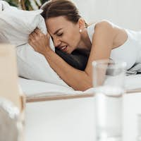 suffering woman in bed and pills with glass of water on foreground
