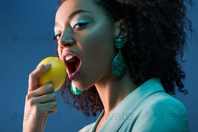 attractive african american woman with braces eating lemon isolated on blue