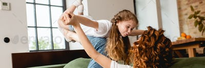 panoramic concept of curly mother lying on sofa, lifting happy daughter and holding hands in living