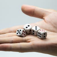 Human hand ready to roll the dice on white isolated background