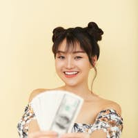 Cheerful Young Woman Holding Money