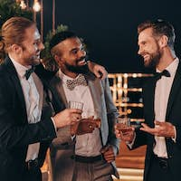 Three handsome men in suits drinking whiskey and communicating while spending time on party