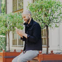 Concentrated male freelancer enjoys day off, breathes fresh air outdoor, uses modern smartphone