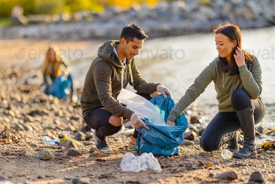 Team of dedicated and smiling volunteers collecting plastic garbage at beach