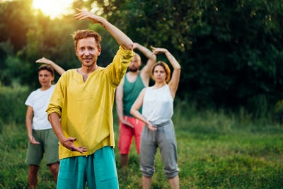 Outdoor group qigong practice with coach.