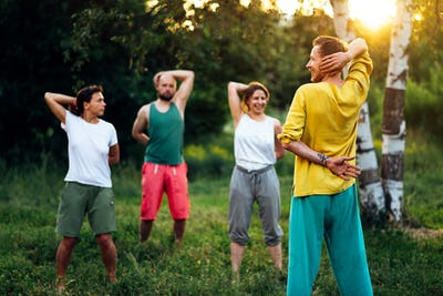 Group qigong practice with trainer in the nature.