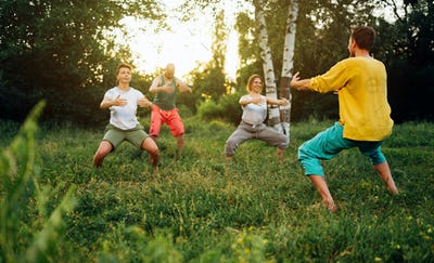 Trainer shows how to do manu stance exercise. Group learning qigong in nature.