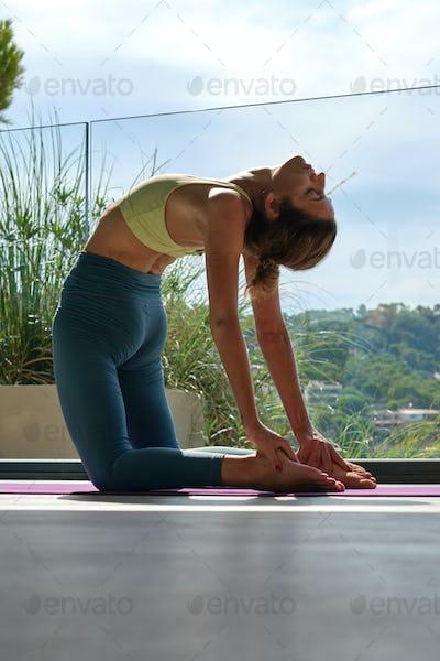Flexible woman doing Camel asana on mat