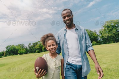 portrait of smiling african american family with rugby ball looking at camera while walking in park