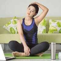 young woman practicing yoga imitating movements from her laptop screen