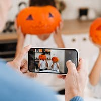 White man taking photo of his children while getting ready for Halloween
