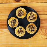 Tartlets with champignons on wooden background