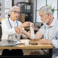 Doctor wrapping bandage on arm of senior man