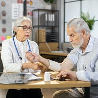 Female middle-aged doctor orthopedist wrapping bandage on arm of senior male patient