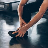 Male athlete suffering from ankle tendon ligament