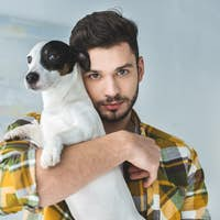 handsome man holding jack russell terrier dog