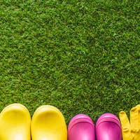 top view of rubber boots, protective gloves and flower pot with gardening tools