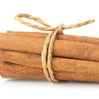 Cinnamon sticks with powder on white background