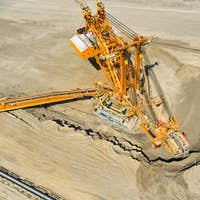 Huge bucket wheel excavator or mobile strip mining machine mining coal in a quarry. Heavy industry