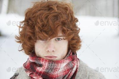 Teenage Boy Wearing Winter Clothes In Snowy Landscape