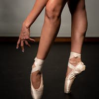Legs of young ballerina with pointe shoes dancing on a black floor. Ballet practice. feet of ballet