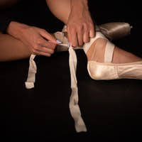 Legs of young ballerina who puts on pointe shoes at black floor background. Ballet practice