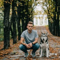 young man with husky dog in autumn park