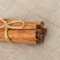 Cinnamon sticks staked on tissue background closeup