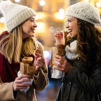 Happy woman friends enjoying time together on christmas market. People happiness concept