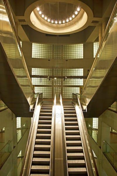 Golden interior escalator in business architecture