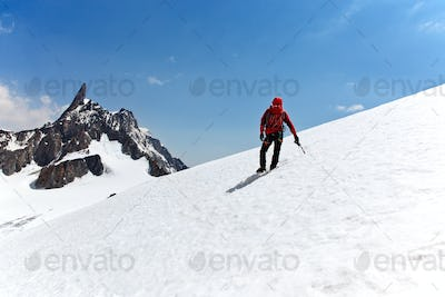 Climber standing on a glacier looking at a mountain peak