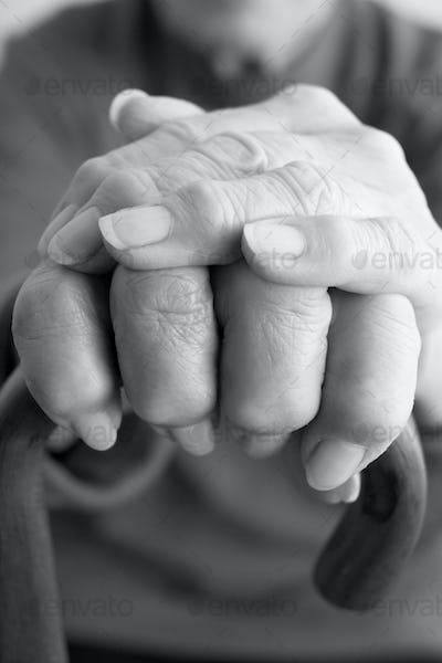 Close-Up Of Elderly Persons Hand Resting On Walking Cane