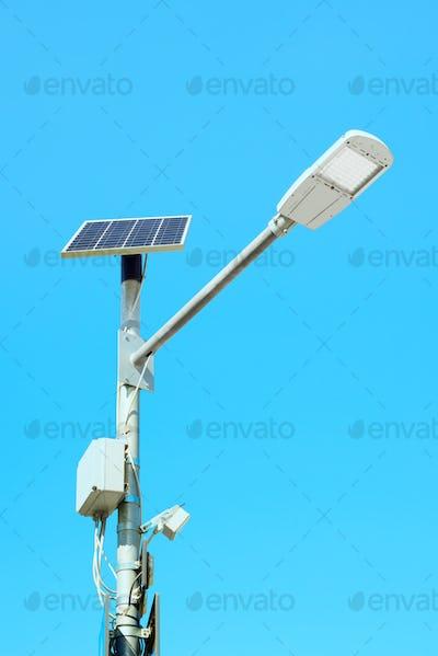 Solar panel powered street light lamp on blue sky background