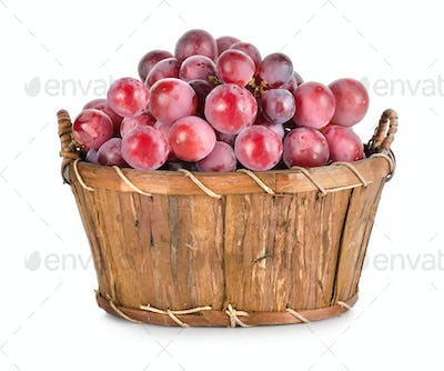 Dark blue grapes in a wooden basket isolated