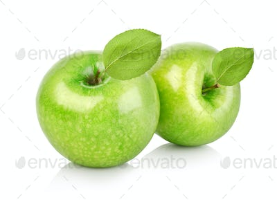 Two green apples with leaves