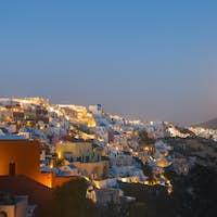 The moon rises over Oia