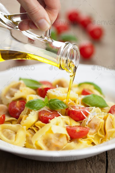 olive oil pouring over tortellini with cheese and tomatoes