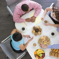 Four businesspeople at boardroom table with breakfast