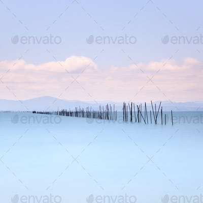 Fishing poles and soft water on sea landscape. Long exposure.