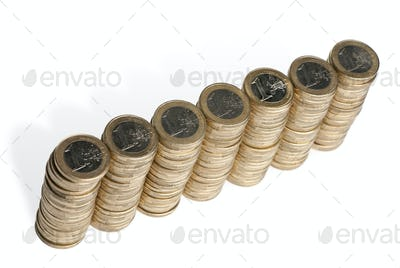 Stacks of 1 Euros Coins in front of white background, high angle view