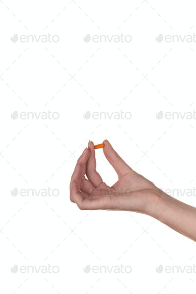 Hand holding an orange capsule isolated on white background