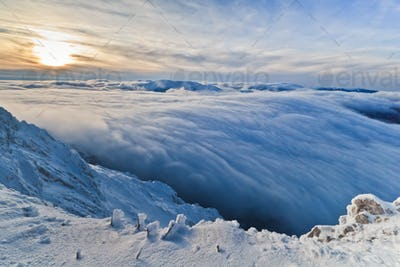 sunset over the mountains and clouds in winter