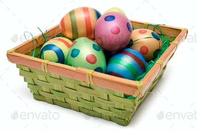 Several Easter Eggs in a Basket Isolated on a White Background