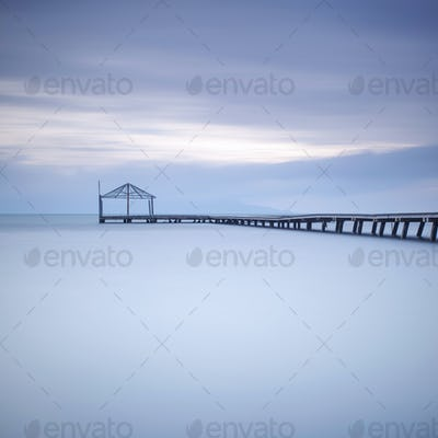 Wooden pier or jetty silhouette and blue ocean on sunset