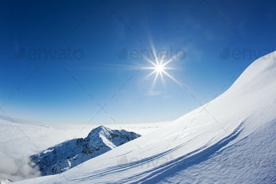 Snowy mountain landscape in a winter clear day. Western Alps, Piemonte, Italy.