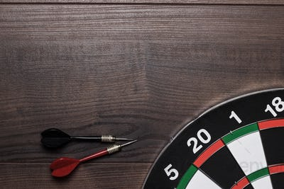 Target And Two Darts On Wooden Table