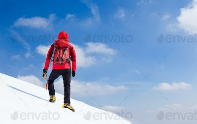 Mountaineer walking uphill along a snowy slope. Rear view. Western Alps, Europe.